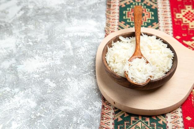 Widok z przodu smaczny gotowany ryż wewnątrz brązowego talerza na białej przestrzeni