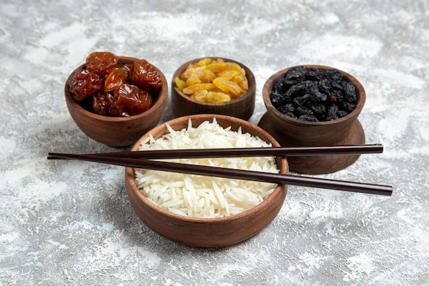 Widok z przodu smaczny gotowany ryż wewnątrz brązowego talerza z rodzynkami na jasnym białym biurku