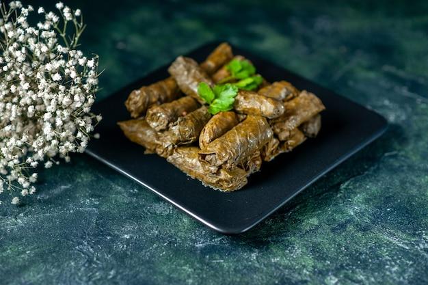 Widok z przodu smaczny liść dolma wewnątrz płyty na ciemnym tle olej kaloryczny obiad jedzenie restauracja posiłek sałatka mięso