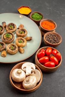 Widok z przodu smaczny posiłek z grzybów ze świeżymi pomidorami i przyprawami na ciemnym daniu na biurko obiadowy posiłek do gotowania grzybów