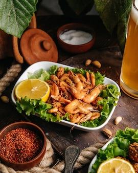 Widok z przodu smażone krewetki z cytryną i zieloną sałatą na stole jedzenie posiłek rak owoców morza
