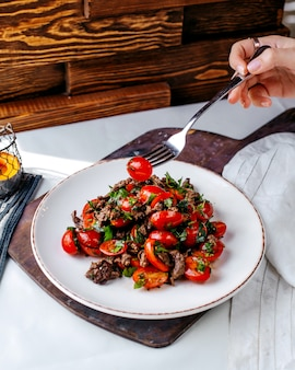 Widok z przodu smażone mięso wraz z czerwonymi pomidorami i fasolą wewnątrz białego talerza na brązowym drewnianym biurku i powierzchni