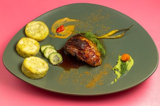 Widok z przodu smażonego mięsa z gotowanymi kabaczkami wewnątrz płyty na różowej powierzchni