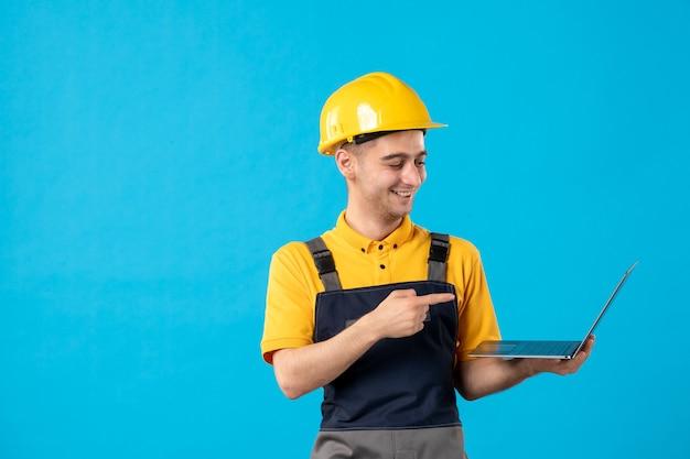 Widok z przodu śmiejącego się pracownika płci męskiej w mundurze z laptopem na niebieskiej powierzchni