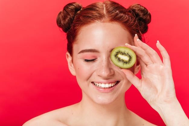 Widok z przodu śmiejącej się kobiety z kiwi. strzał studio podekscytowana dziewczyna imbir z egzotycznymi owocami.