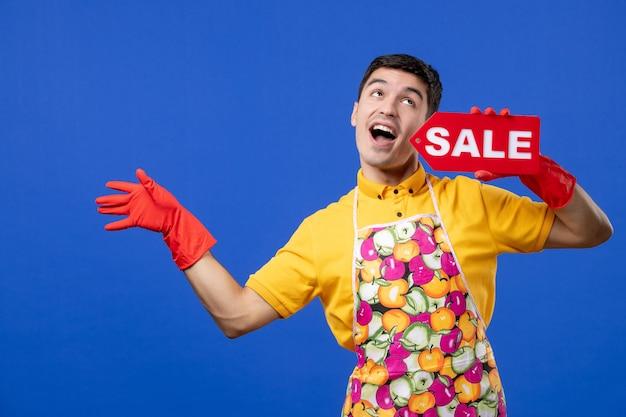 Widok z przodu śmieszna męska gospodyni w czerwonych rękawiczkach odpływowych trzymająca znak sprzedaży na niebieskiej przestrzeni