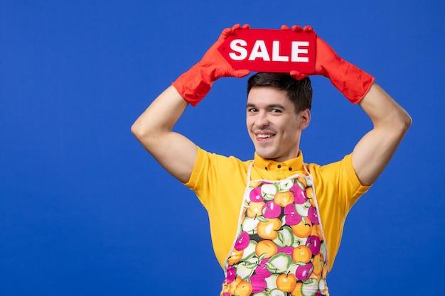 Widok z przodu śmieszna męska gospodyni w żółtej koszulce podnosząca znak sprzedaży nad głową na niebieskiej przestrzeni