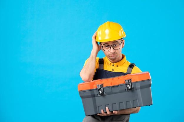 Widok z przodu smutny konstruktor płci męskiej w mundurze z skrzynką narzędziową w rękach na niebiesko
