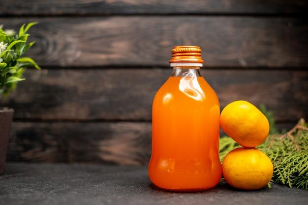 Widok z przodu sok pomarańczowy w butelce świeże pomarańcze gałęzie sosny na brązowej izolowanej powierzchni