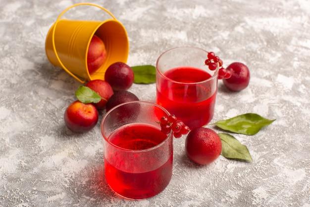 Widok z przodu sok śliwkowy zabarwiony na czerwono ze świeżymi śliwkami na szarym tle