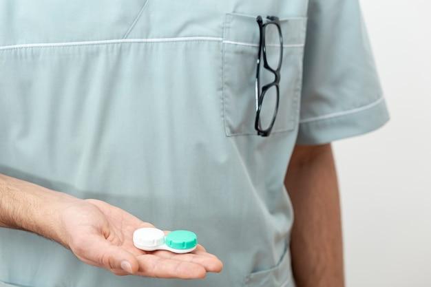 Widok z przodu specjalizującego się w oku specjalisty trzymającego futerał na szkła kontaktowe