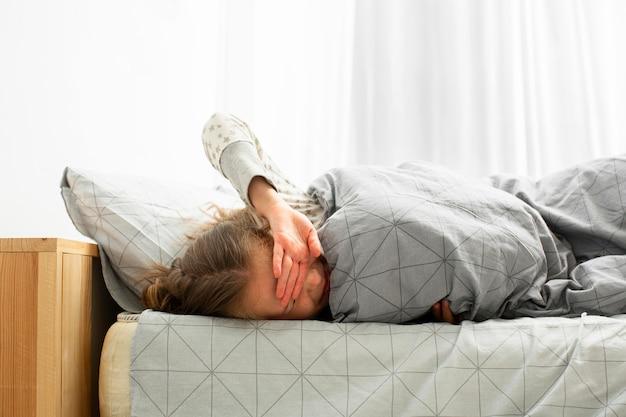 Widok z przodu śpiącej dziewczyny budzi się