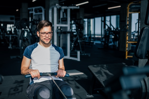 Widok z przodu sportowca w sportowej robi wioślarstwo w siłowni.
