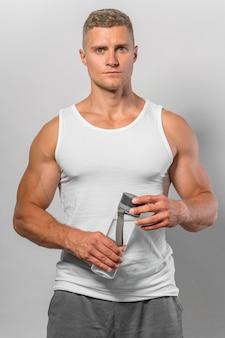 Widok z przodu sprawnego mężczyzny w szczycie zbiornika trzymającego butelkę wody