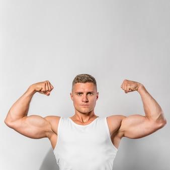 Widok z przodu sprawny mężczyzna pokazujący bicepsy z miejsca na kopię