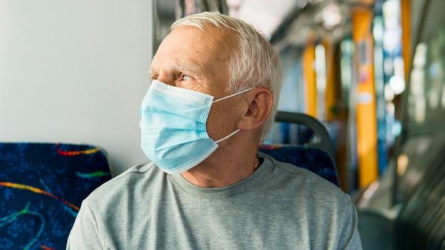 Widok z przodu starego człowieka w transporcie publicznym