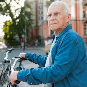 Widok z przodu starego człowieka z rowerem