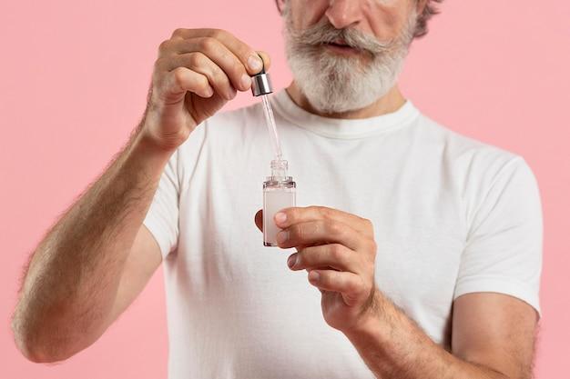 Widok z przodu starszego brodatego mężczyzny używającego serum