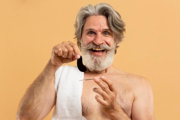 Widok z przodu starszego mężczyzny z brodą trzymającego opaski na oczy