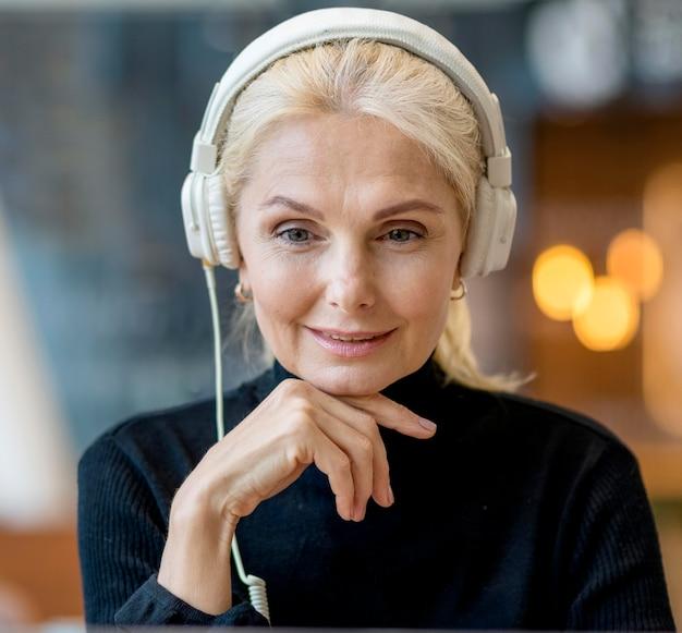 Widok z przodu starszej kobiety biznesu na rozmowę konferencyjną ze słuchawkami