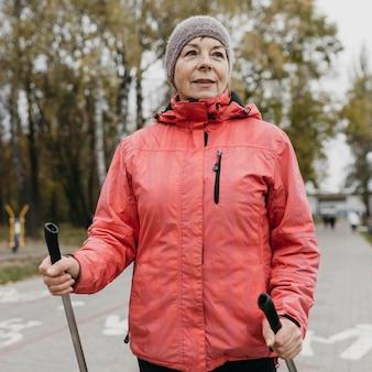 Widok z przodu starszej kobiety na zewnątrz z kijami trekkingowymi