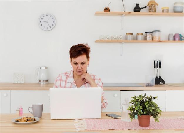 Widok z przodu starszej kobiety w domu na swoim laptopie