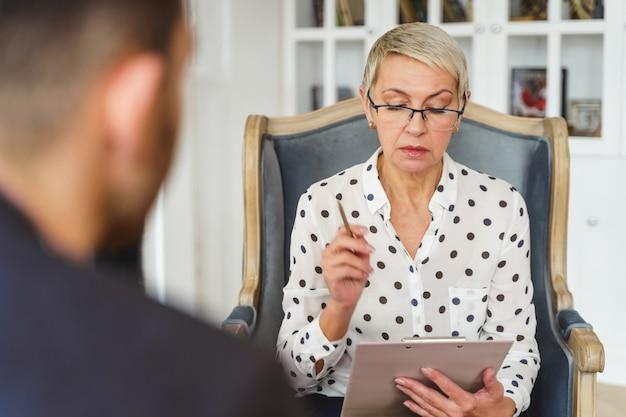 Widok z przodu starszej psychoterapeutki wpatrującej się w swoje notatki podczas sesji terapeutycznej