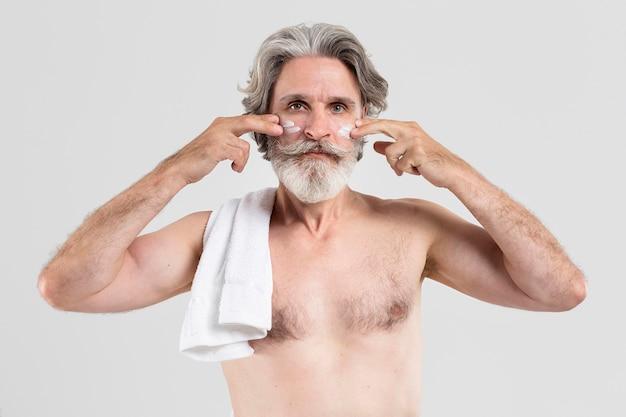 Widok z przodu starszy mężczyzna z ręcznikiem stosując balsam