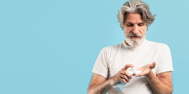 Widok z przodu starszy mężczyzna za pomocą środka czyszczącego