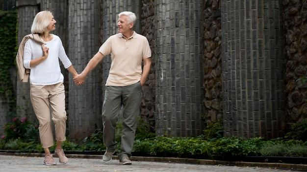 Widok z przodu starszy para trzymając się za ręce podczas spaceru na świeżym powietrzu