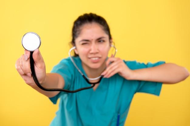 Widok z przodu stetoskopu w ręce lekarza kobiet na żółtej ścianie na białym tle