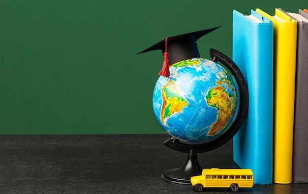Widok z przodu stosu książek z czapką akademicką i szkolnym autobusem