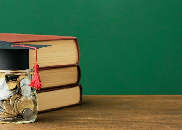 Widok z przodu stosu książek z miejscem na kopię i słoik monet