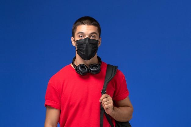 Widok z przodu student w czerwonej koszulce na sobie maskę z plecakiem na niebieskim tle.