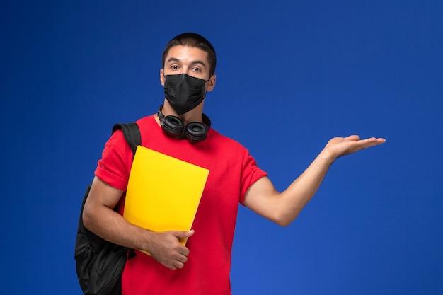 Widok z przodu student w czerwonej koszulce na sobie maskę z plecakiem trzymając żółty plik na niebieskim tle.