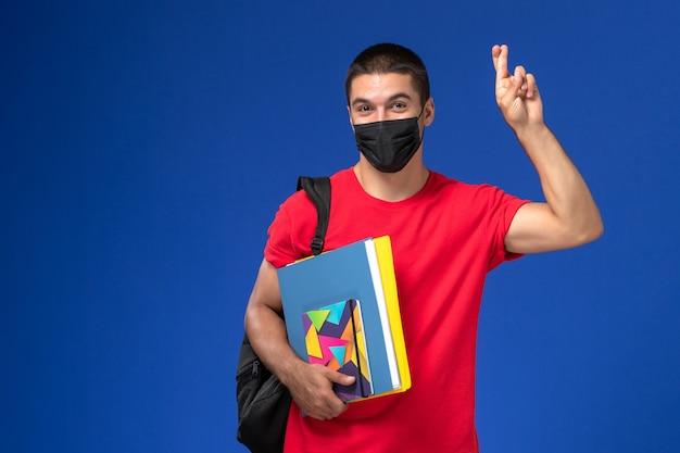 Widok z przodu student w czerwonej koszulce na sobie plecak w czarnej sterylnej masce, trzymając zeszyt i pliki na niebieskim tle.