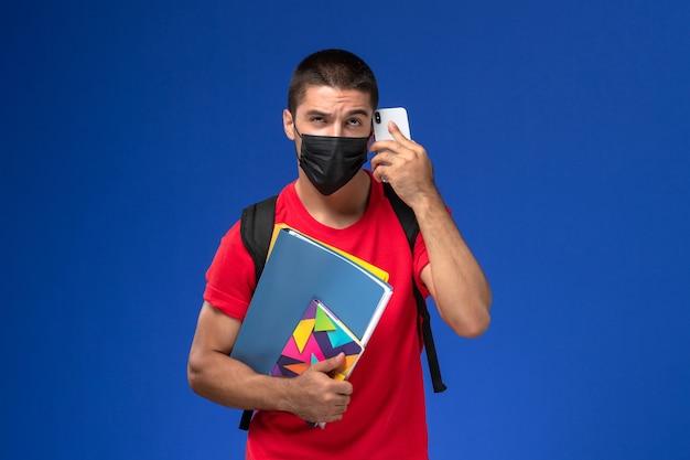 Widok z przodu student w czerwonej koszulce na sobie plecak z maską, trzymając pliki zeszytu rozmawia przez telefon na niebieskim tle.