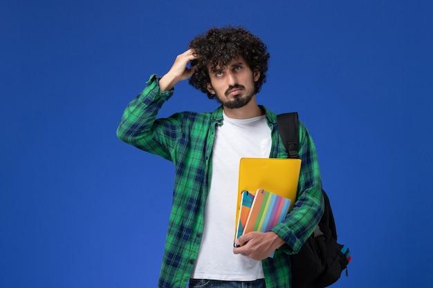 Widok z przodu studenta na sobie czarny plecak, trzymając zeszyty i pliki myślenia na niebieskiej ścianie