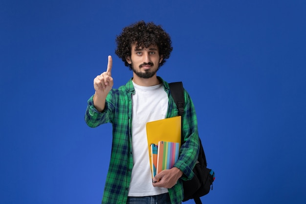 Widok z przodu studenta na sobie czarny plecak, trzymając zeszyty i pliki na niebieskiej ścianie