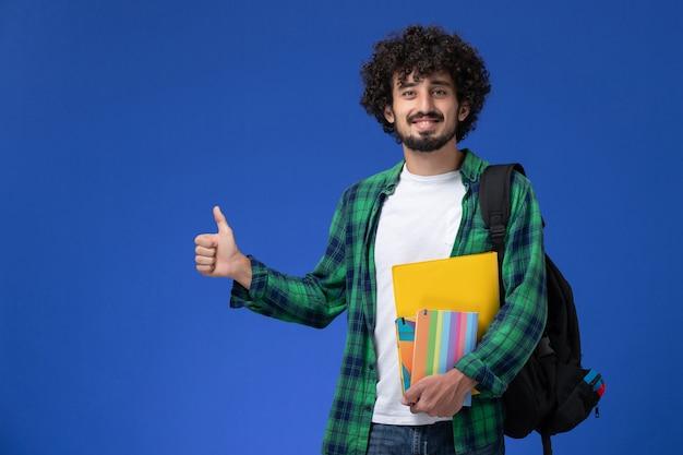 Widok z przodu studenta na sobie czarny plecak, trzymając zeszyty i uśmiechając się na niebieskiej ścianie