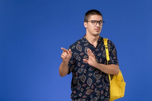 Widok z przodu studenta na sobie żółty plecak z niezadowolonym wyrazem twarzy na niebieskiej ścianie