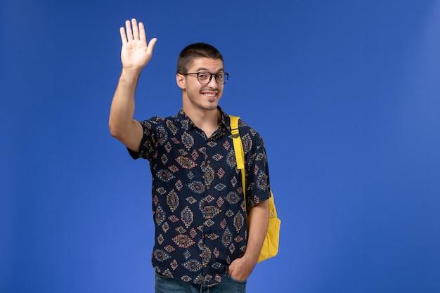 Widok z przodu studenta w ciemnej bawełnianej koszuli w żółtym plecaku, machając ręką na niebieskiej ścianie
