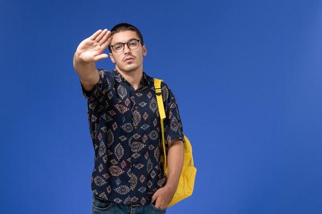 Widok z przodu studenta w ciemnej bawełnianej koszuli w żółtym plecaku pozującym na jasnoniebieskiej ścianie