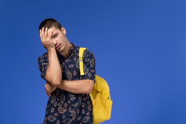 Widok z przodu studenta w ciemnej bawełnianej koszuli w żółtym plecaku zmęczonego chłopca na jasnoniebieskiej ścianie