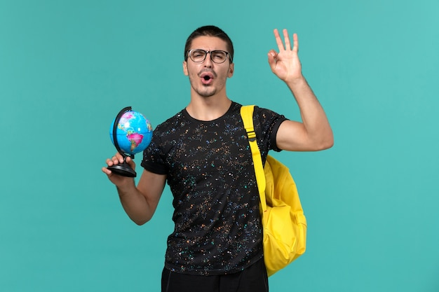 Widok z przodu studenta w ciemnej koszulce żółty plecak trzymający małą kulę ziemską na niebieskiej ścianie
