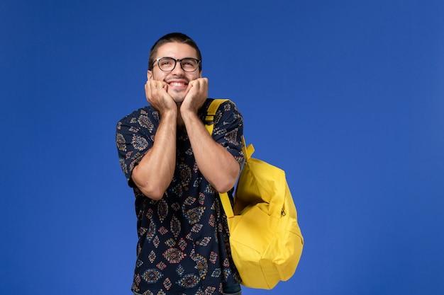 Widok z przodu studenta w ciemnej koszuli na sobie żółty plecak z radosnym wyrazem twarzy na niebieskiej ścianie