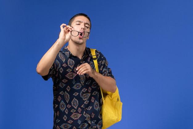 Widok z przodu studenta w ciemnej koszuli w żółtym plecaku, czyszczącego okulary przeciwsłoneczne na jasnoniebieskiej ścianie