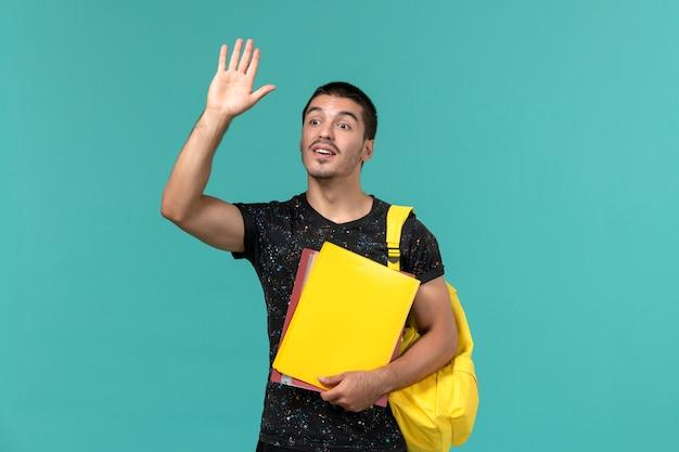 Widok z przodu studenta w ciemnym t-shirt żółtym plecaku trzymającym różne pliki machając na jasnoniebieskiej ścianie