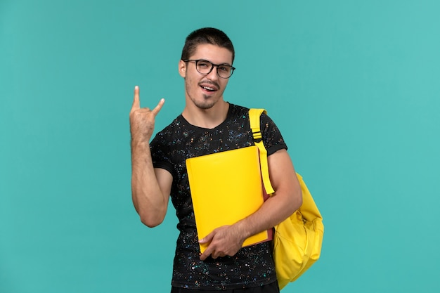 Widok z przodu studenta w ciemnym żółtym plecaku t-shirt trzymającym różne pliki na jasnoniebieskiej ścianie