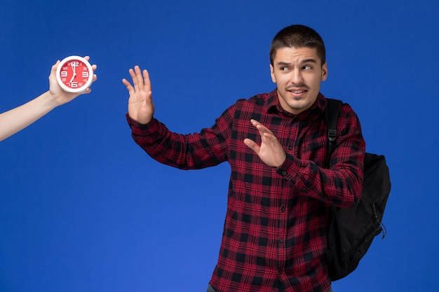 Widok z przodu studenta w czerwonej koszuli w kratkę z plecakiem boi się zegarów na niebieskiej ścianie